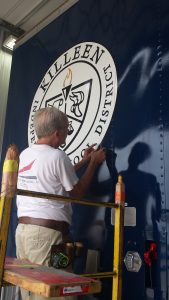 Killeen ISD Seal on Band Semi Trailers being applied to Shoemaker Band Trailer